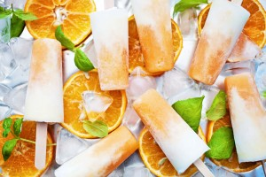 Orange cream popsicles with orange slices, basil, and ice